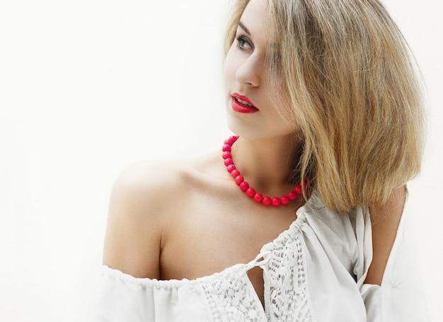 Hermosa rubia encantadora con cabello largo sentada en la cama en una habitación blanca