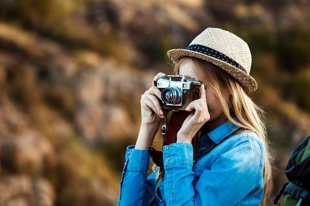 Hermosa rubia fotógrafa tomando foto del paisaje del cañón