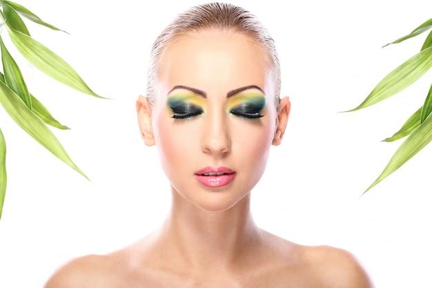 Hermosa rubia con hojas de bambú