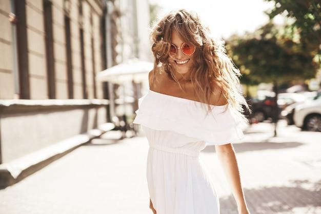 Hermosa rubia linda modelo adolescente sin maquillaje en verano hipster vestido blanco corriendo en la calle con gafas de sol. date la vuelta y corriendo