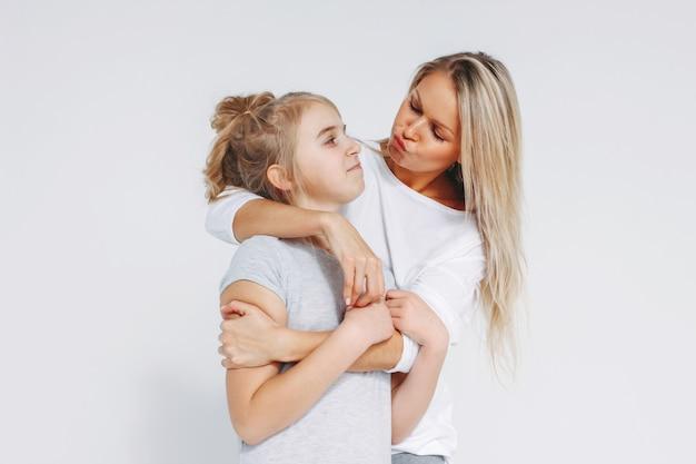 Hermosa rubia madre e hija preadolescente en pijama abrazando y divirtiéndose aislado sobre fondo blanco.