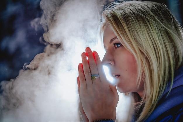 Hermosa rubia de ojos azules calienta sus manos en el frío de la noche