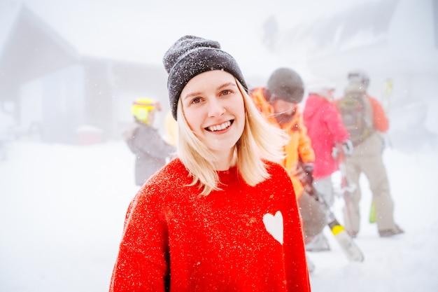 Hermosa rubia de ojos azules con un suéter rojo con un corazón blanco sonríe bajo la nieve.