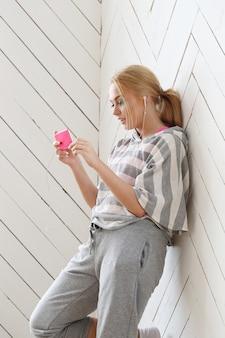 Hermosa rubia en la pared con teléfono rosa