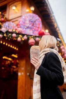 Hermosa rubia con pastel de saliva en el mercado de navidad en wroclaw, polonia