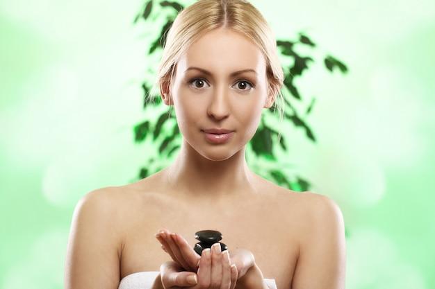 Hermosa rubia con piedras zen en mano