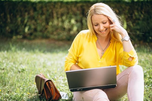 Hermosa rubia sentada en la hierba y trabajando en la computadora portátil