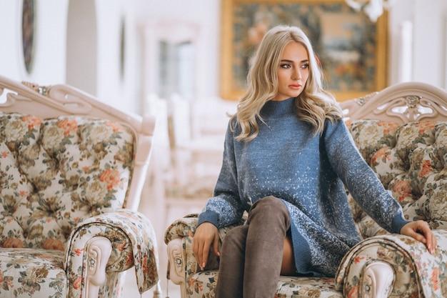 Hermosa rubia sentada en el sofá