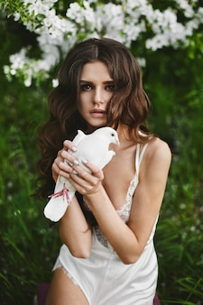 Hermosa y sensual mujer modelo de cabello castaño con maquillaje suave y peinado elegante, en lencería de satén de moda, posando con la paloma en sus manos al aire libre en el bosque verde