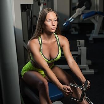 Hermosa sexy atlética muscular joven. chica caucásica fitness entrena en el gimnasio