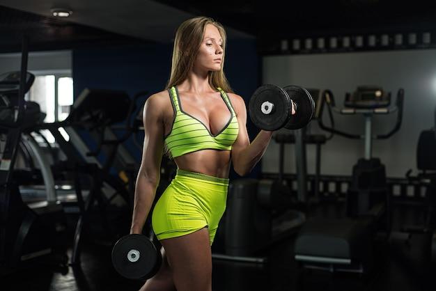 Hermosa sexy atlética muscular joven. chica fitness entrena en el gimnasio, haciendo ejercicios con una barra