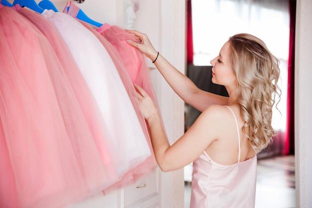 Una hermosa y sexy chica rubia en pijama rosa elige un atuendo en una percha. la niña está en su dormitorio.