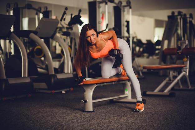 Hermosa y sexy mujer haciendo ejercicios con mancuernas.