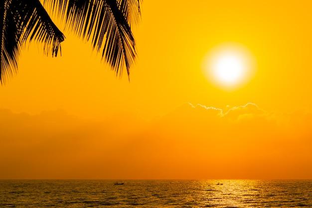 Hermosa silueta de palmera de coco en el cielo de la playa del océano cerca del mar al atardecer o al amanecer