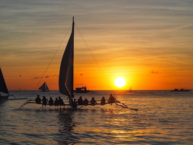 Hermosa silueta de la puesta de sol en el mar y los viajeros en velero en boraycay philippin