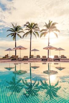 Hermosa sombrilla de lujo y una silla alrededor de la piscina al aire libre en el hotel y resort con palmera de coco en el cielo al atardecer o al amanecer