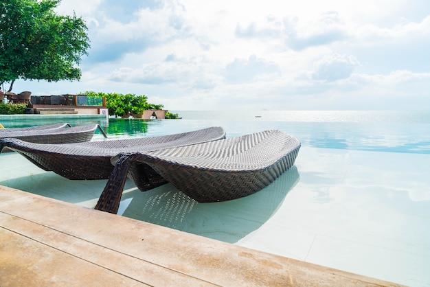 Hermosa sombrilla de lujo y una silla alrededor de la piscina al aire libre en el hotel y resort