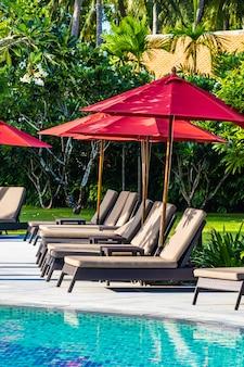 Hermosa sombrilla y silla alrededor de la piscina al aire libre en el complejo hotelero para viajes de vacaciones