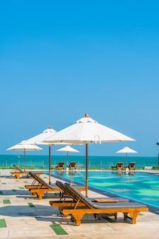 Hermosa sombrilla y silla alrededor de la piscina en hotel y resort