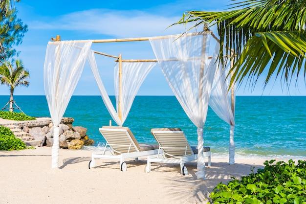 Hermosa sombrilla y silla alrededor de playa mar océano con cielo azul para viajar