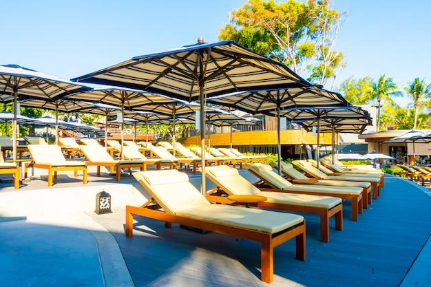 Hermosa sombrilla y silla de lujo alrededor de la piscina al aire libre en el hotel y resort con palmera de coco