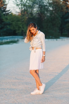 Hermosa y sonriente chica de moda posando en un elegante y femenino
