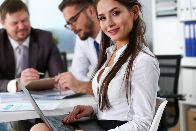 Hermosa sonriente chica morena secretaria en el lugar de trabajo