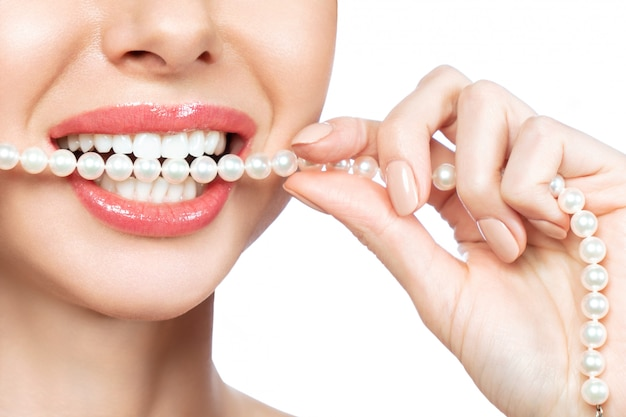 Hermosa sonrisa femenina y collar de perlas, concepto de salud dental