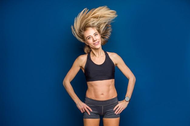 Hermosa sonrisa forma joven en sujetador deportivo con el pelo que fluye. baile, gimnasio, concepto delgado