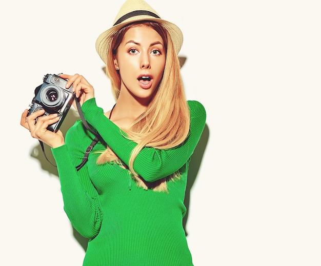 Hermosa sorpresa feliz linda mujer rubia niña en ropa casual verano verde hipster toma fotos con cámara fotográfica retro,