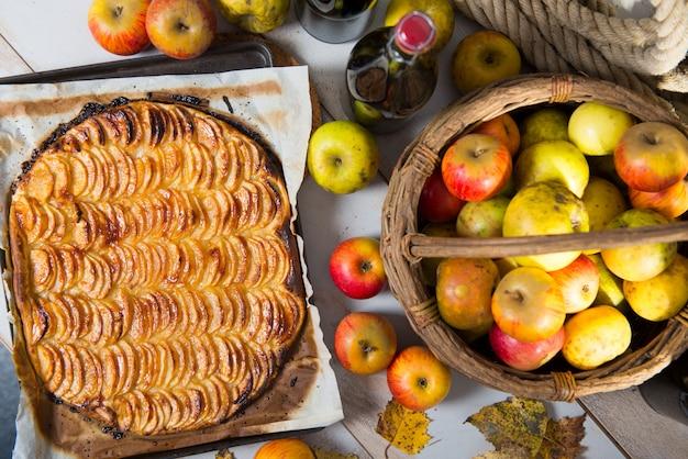Hermosa tarta de manzana con una cesta de manzanas