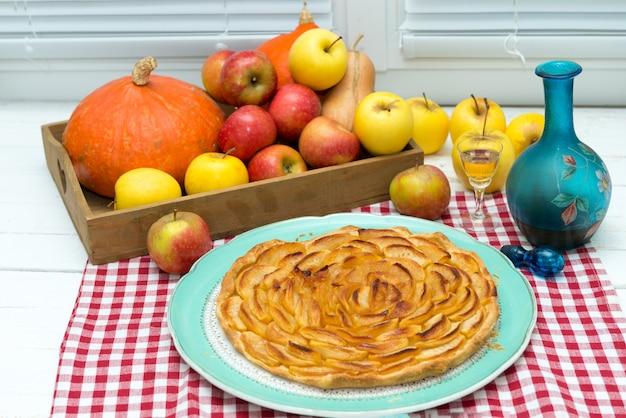 Hermosa tarta de manzana con manzanas y vaso de calvados