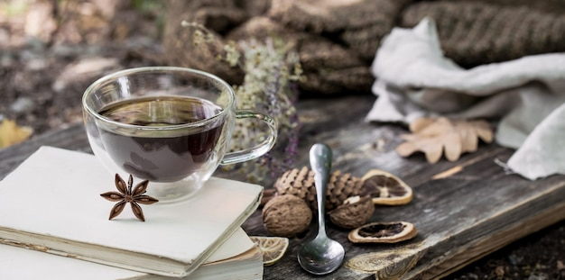 Hermosa taza de té transparente con hojas de otoño y limón seco sobre un palé de madera sobre fondo de naturaleza