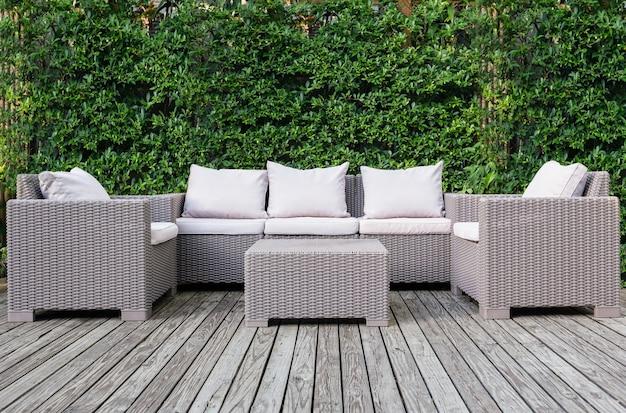 Hermosa terraza de madera con muebles de jardín de ratán con fondo verde