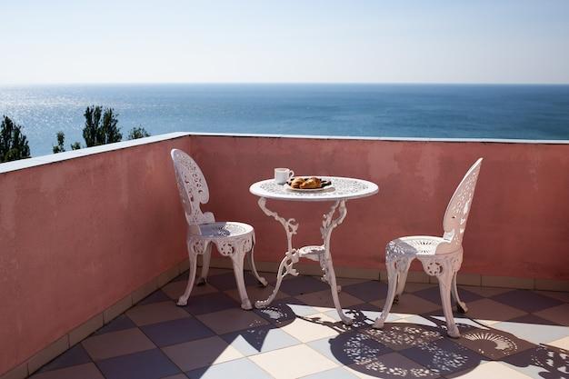 Hermosa terraza con sillas y una mesa con una hermosa vista al mar