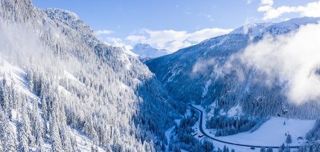 Hermosa toma aérea de los alpes cubiertos de árboles durante un invierno nevado en suiza