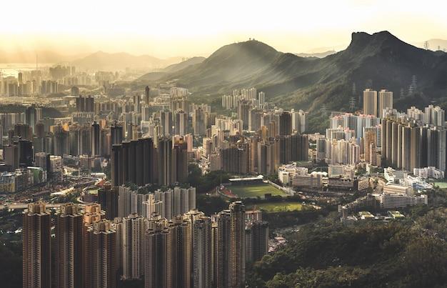 Hermosa toma aérea del área del edificio de apartamentos junto a altas montañas y colinas en un día soleado