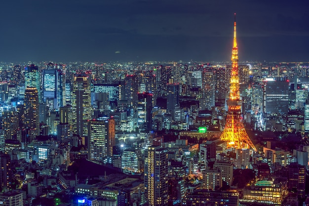 Hermosa toma aérea de la arquitectura moderna de la ciudad con una torre iluminada en el lateral