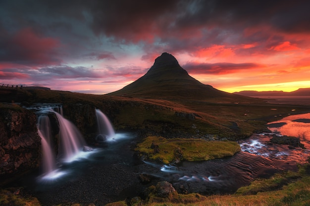 Hermosa toma aérea de una cascada rodeada de colina al atardecer