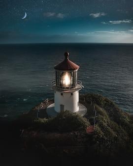Hermosa toma aérea de un faro iluminado en una colina verde con la media luna en el cielo nocturno