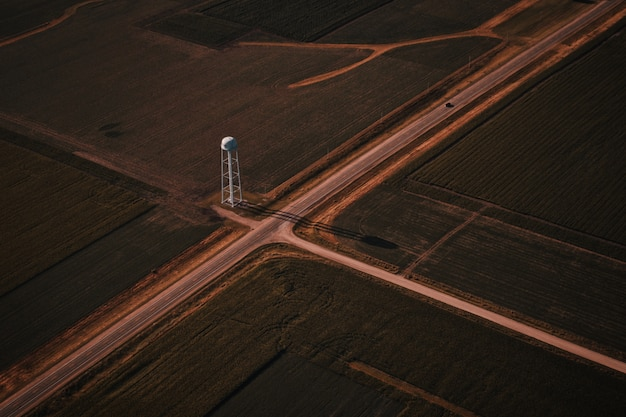 Hermosa toma aérea de intersección de carreteras estrechas en el campo con una torre blanca