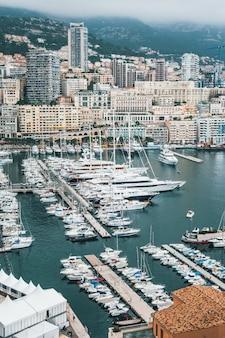 Hermosa toma aérea de un muelle con muchos barcos estacionados y una ciudad urbana en el fondo