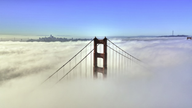Hermosa toma aérea de la parte superior de un puente rodeado de nubes y cielo azul