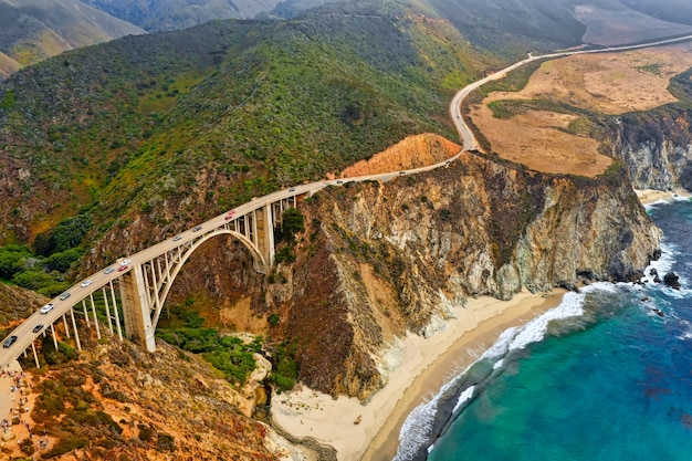 Hermosa toma aérea de verdes colinas y un puente estrecho y curvilíneo que recorre los acantilados