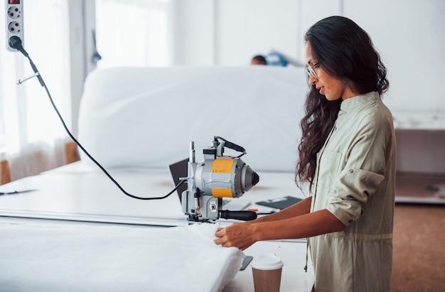 Hermosa trabajadora con gafas está en la fábrica de costura.