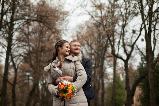 Hermosa ucraniana novia y el novio en trajes de bordado nativo en el fondo de los árboles en un parque, ceremonia tradicional de la boda