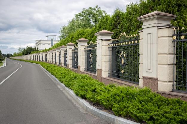 Hermosa valla de piedra larga con puertas de metal forjado pintadas con oro