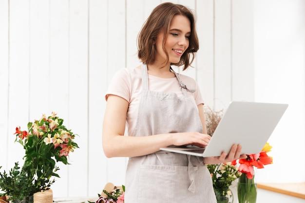Hermosa vendedora de pie cerca de ramos de flores en el taller de flores y usando laptop