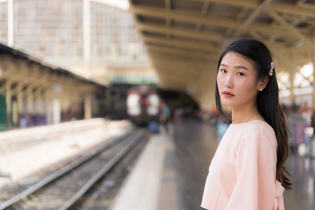 Hermosa viajera esperando el tren en la estación