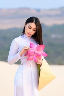 Hermosa vietnamita con loto rosa en el desierto de dunas de arena blanca, muine, vietnam